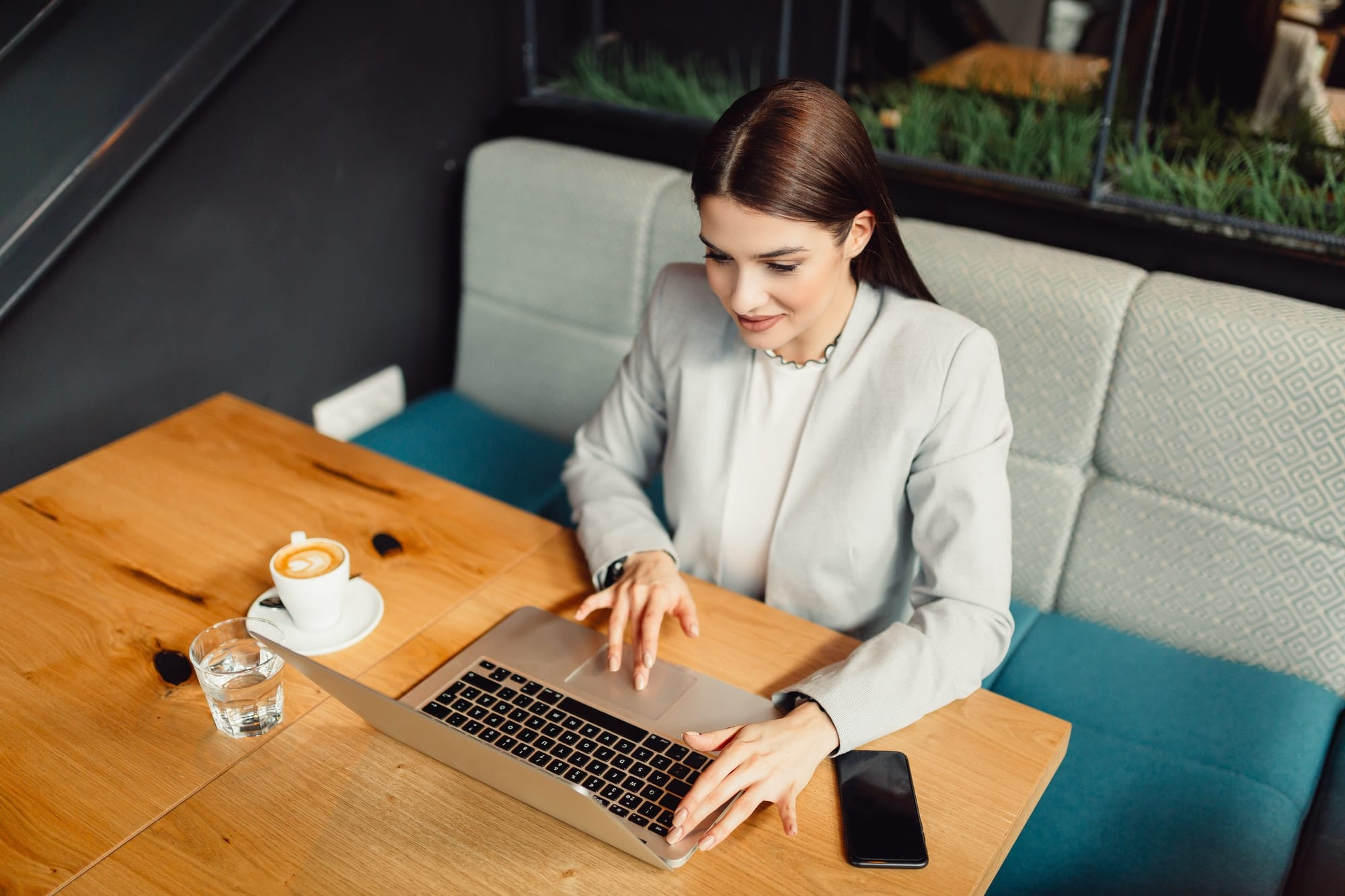 Pretty business woman using laptop in cafe. Business, online business concept.